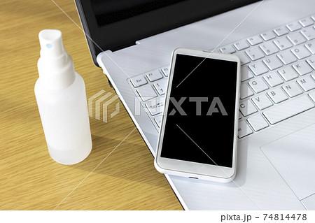 ノートパソコンとスマートフォンをアルコール消毒するイメージ 74814478