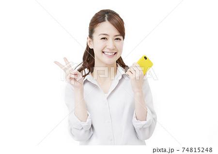 スマホを持つ女性 ピースサイン 74815248