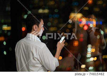 夜のオフィスでスマホを使うビジネスマン 74815462