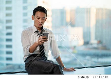 オフィスでスマホを使うビジネスマン 74815716