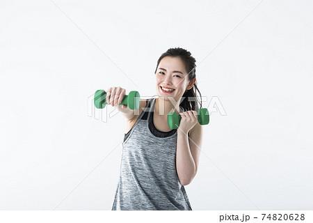 若い女性 スポーツウェア 白バック カメラ目線 ダンベル パンチ 74820628