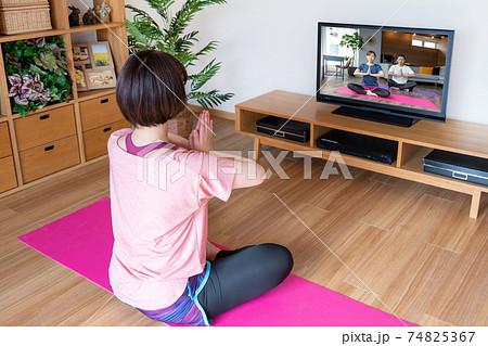 オンラインヨガ リビングでテレビの画面を見ながらヨガの合掌ポーズをする若い女性 74825367