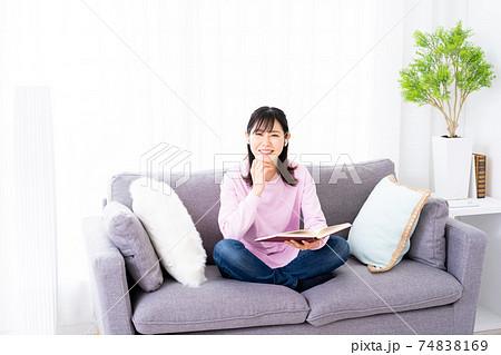 ソファーで音楽を聴きながら読書をする若い女性 74838169