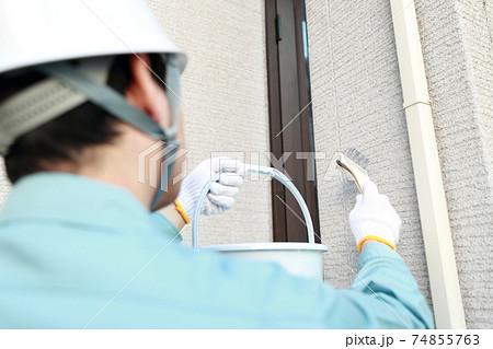 一軒家の外壁に塗装をする作業員の男性 74855763