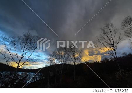 小沼の上にかかるカラフルに染まる雲と夕景 74858052