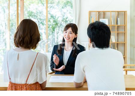 若い夫婦に説明する若いビジネスウーマン  74890705
