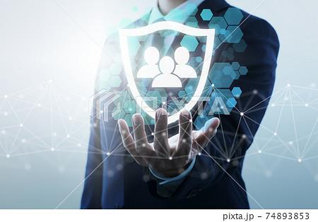 個人情報の保護。ネットワークセキュリティのイメージ。盾のアイコンを持つ男性。 74893853