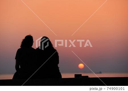 海岸で座って綺麗な夕焼けを見ているカップルの姿 74900101