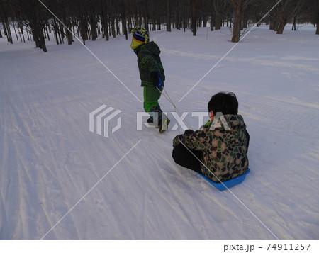 真っ白になった公園でそりで遊ぶ子ども(後ろ姿) 74911257