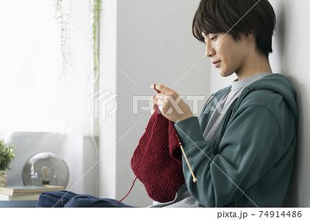 編み物をする若い男性の横顔 74914486