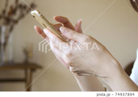 リビングでスマートフォンを見る女性の手 74937894