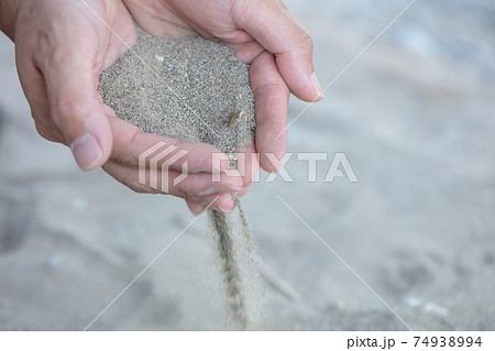 河原砂を手にすくってサラサラとこぼす写真 74938994