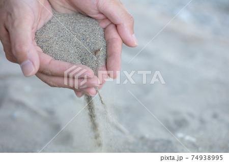 河原砂を手にすくってサラサラとこぼす写真 74938995
