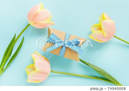 青の背景にチューリップの花とギフトボックス 74940008