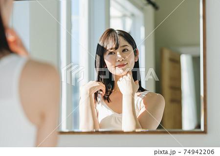 洗面所の鏡を見る女性 74942206