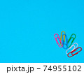 Collection of colorful paper clips on blue background 74955102