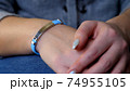 Female hand with vaccined bracelet or label after injection 74955105