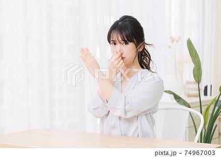 部屋で鼻をつまむ若い女性 74967003