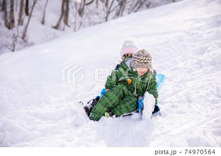 女の子と男の子の子供がスキー場でそりで遊んでいる 74970564