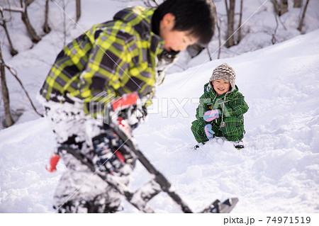 スキー場でスキーウェアーを着て兄弟で遊んでいる winter 74971519