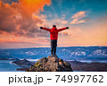 Traveler man wear red clothes and raising arm standing on mountain at sunset in Lake Baikal, Siberia, Russia. 74997762