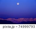 朝日を受ける雪山と満月 74999793