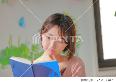 あごに手を当て「難しいなあ」と感じながらビジネス書を読む女性 75013387