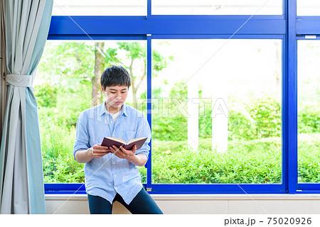 大学の教室、講義室で教科書を開いて読む大学生 75020926