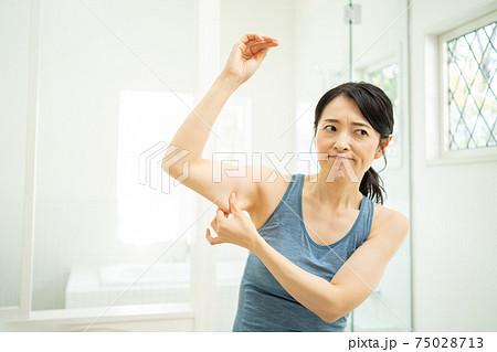 二の腕を気にする女性 75028713