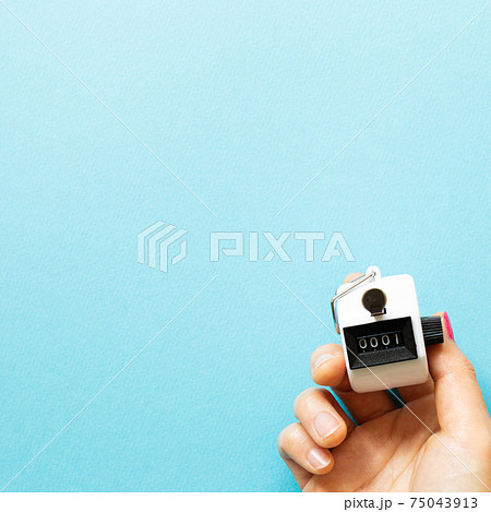 Hand tally counter on blue background. top view, copy space 75043913