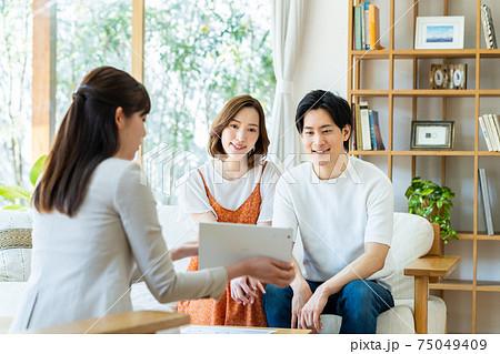 タブレットで若い夫婦に説明するビジネスウーマン 75049409