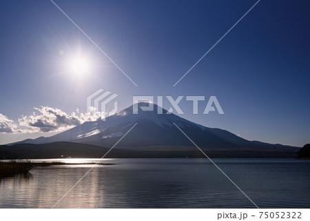 夕暮れ前の沈む太陽と富士のシルエット 75052322