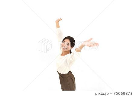 空を仰いで両手を広げるカジュアルの女性2 白背景 75069873