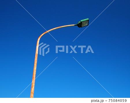 ペンキの剥げたポールの街路灯と青空 75084059