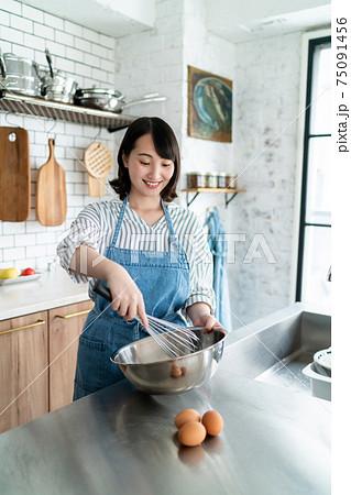 キッチンでお菓子作りをする女性 75091456