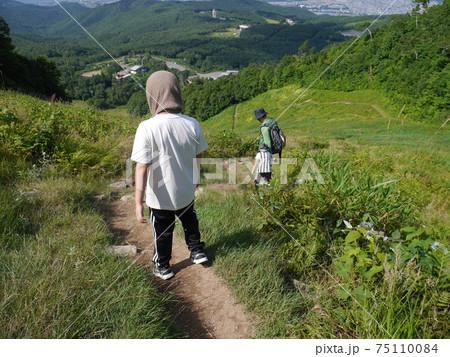 緑溢れる夏に軽登山する親子の後ろ姿(下山) 75110084