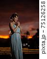 夕暮れの公園に立ってお願いのポーズをとるハーフの女性 75126258