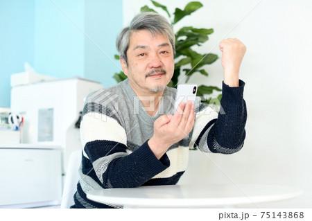 ガッツポーズをしながらスマホを操作する中高年(シニア)の白髪男性 75143868
