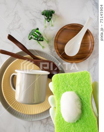 大理石カウンターの上の食器と食器用洗剤のついたスポンジ 75145904