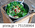 Woman Cooking Stir Fried Kale with Pork on the Simple Bonfire at Camping in Backyard. 75158964