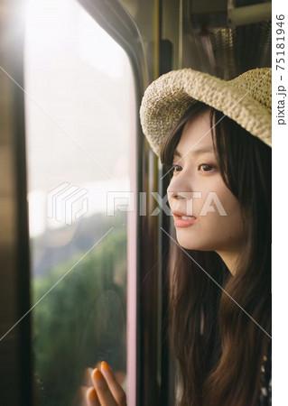電車で窓の外の景色を眺めている麦わら帽子の女性 75181946