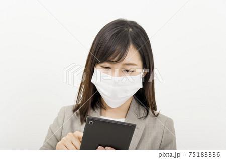 タブレットを使っているマスク姿の女性 75183336
