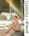 ケアンズのラグーンプールに座るハーフの美女 75200371