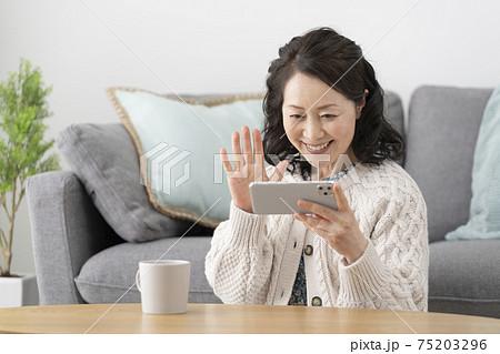 スマートフォンの画面に向かって手を振る笑顔の60代女性 75203296
