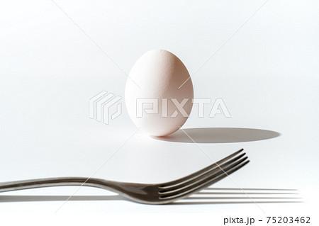 立っている卵とフォーク(卵を食べるイメージ) 75203462