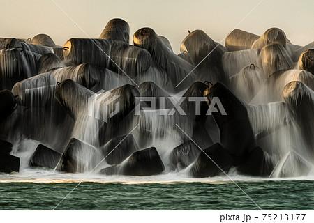 屋久島安房港の夜明け。テトラポットに砕ける波と光の絶景 75213177