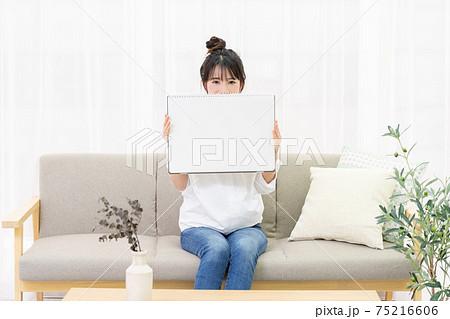 ソファに座って大きいスケッチブックを持つ若い女性 75216606