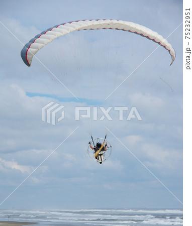 海岸の上を飛ぶパラモーター 75232951