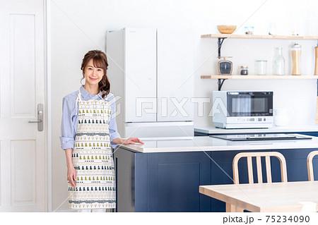 キッチンに立つ笑顔の若い女性 75234090