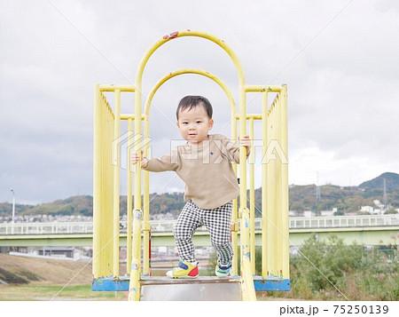 見晴らしの良いすべり台で遊ぶ子供 75250139
